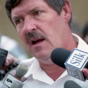 Man speaking into several microphones. Wears a white shirt.