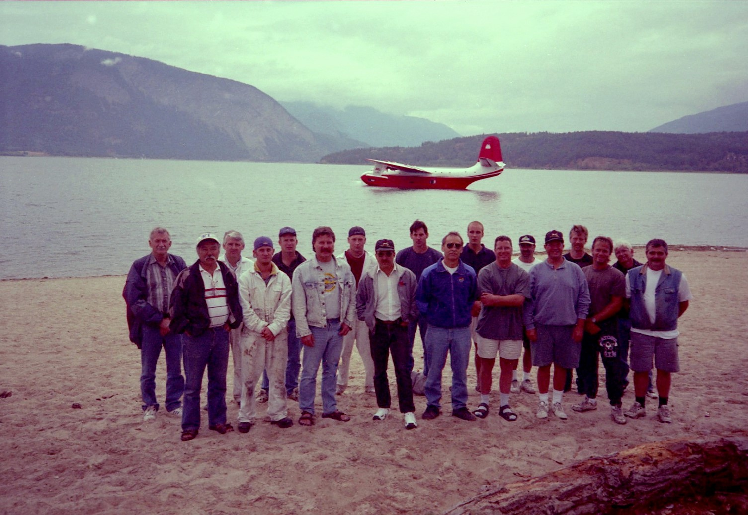 18 men stand on shore in front of a float aeroplane.