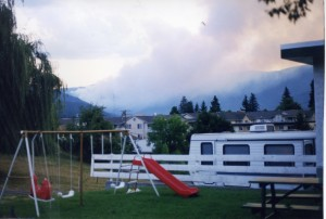 Fire burning in hills. Smokey background. Children's swing set in foreground.