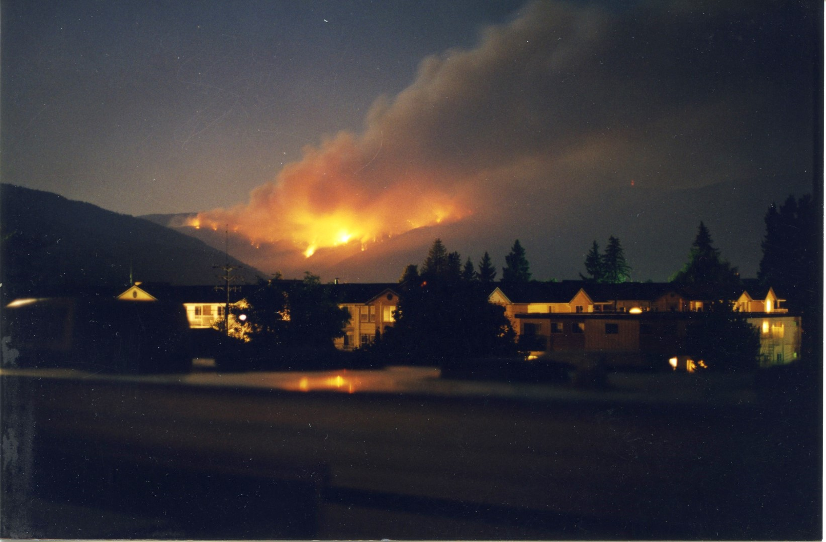 Fire burns bright red at night. Buildings lit in the foreground.