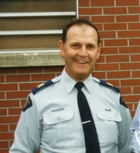 Man in police uniform smiles.