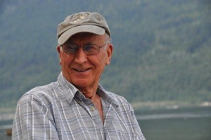 Man in a baseball cap smiles, lake and hillside in background.