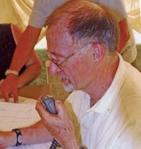 Portrait of a man speaking into a hand held radio speaker.