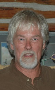 Portrait of a silver haired man with a goatee looking directly ahead.