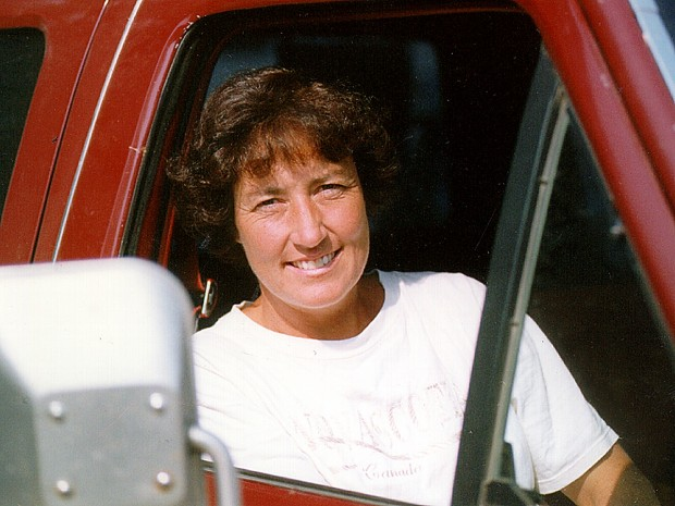 Woman sits in passenger seat of a red truck.