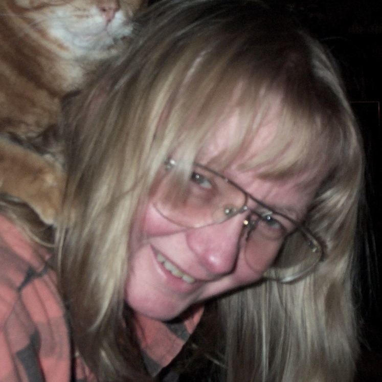 Portrait of a blond woman wearing glasses with a cat on her shoulders.