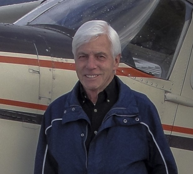 Portrait of a silver haired man standing in front of an aeroplane.