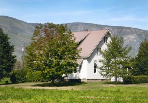 Maison blanche, toit rose, 2 arbres en avant. Collines en arrière-plan.