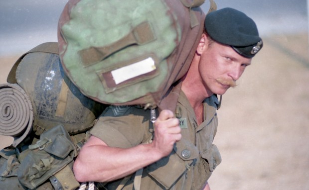 Soldier in uniform carries his personal gear.