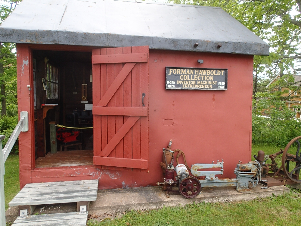 A small red metal building, with a doorway leading inside. A Hawboldt jet pump sitting in front with a sign that says Forman Hawboldt Collection.