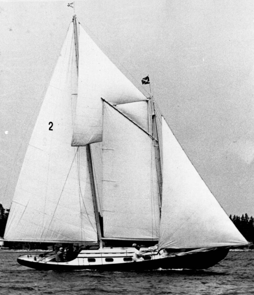 "A black and white photo of the schooner, ""Airlie"" under full sail in the harbour. The ""Airlie"" is black with a white cabin, white sails and an identifying number 2 on the main sail of the 5 she is flying in the picture. Schooners like this one were used for fishing and were quickly adapted to accept the new make and break engines. Today they are used mainly as pleasure craft."