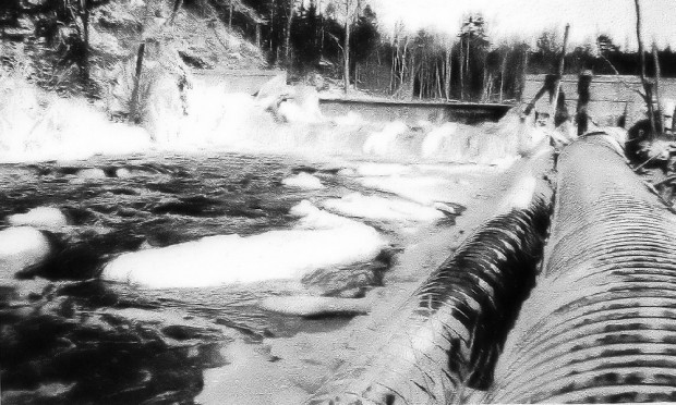 A black and white photo showing the dam on the East River with the gates closed, the water swirling at the foot of the dam and then continuing down the river. On the bank to the right, two large pipes that carried the water to the generating station.