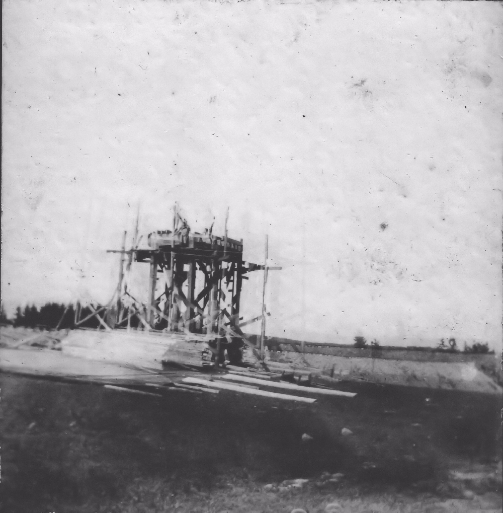 A black and white photograph showing the framework of a water tower being constructed with piles of lumber in the foreground and the embankment of the Halifax and Southwestern Railway bed in the background. This tower was to supply water for the village water supply and the trains.
