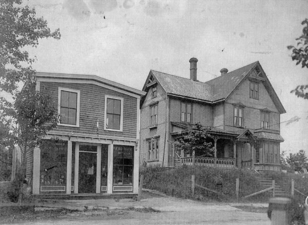 A black and white photo of the two-storey jewelry store with two shop windows and a door in the middle, close to the road. The top floor has two smaller windows. To the right on a rise, set back from the road, with a wire fence by the street, a three storey shingled house with steps leading up to the front door, dormer windows on the right of the front steps and a veranda along the left front of the house. The house sports gingerbread trim, many windows and a steeply pitched roof.