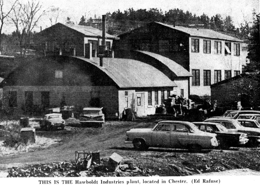 A black and white photo of the company showing the office on North Street with the two-storey machine shop at the back and the domed roof welding and foundry buildings to the left of the machine shop. The worker's parking lot is shown in the foreground next to the stream.