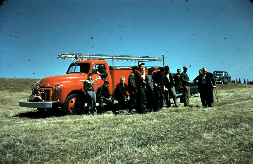 Une photo en couleur montrant, vers 1937, le premier camion de pompiers rouge avec les pompiers se tenant devant lui. Le camion a une échelle sur le toit et une pompe à eau sur le pare-choc avant.