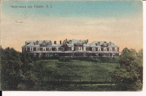 A colour post card showing a large three section reddish building with a green roof perched on a hill top overlooking the Back Harbour, Chester, known as the Hackmatack Inn. A veranda runs along the front of two sections of the building and tennis courts are visible in the foreground. This was one of the large hotels that received water from Hawboldt Gas Engines and its developer Mr. Keasby was one of the original investors in the project.