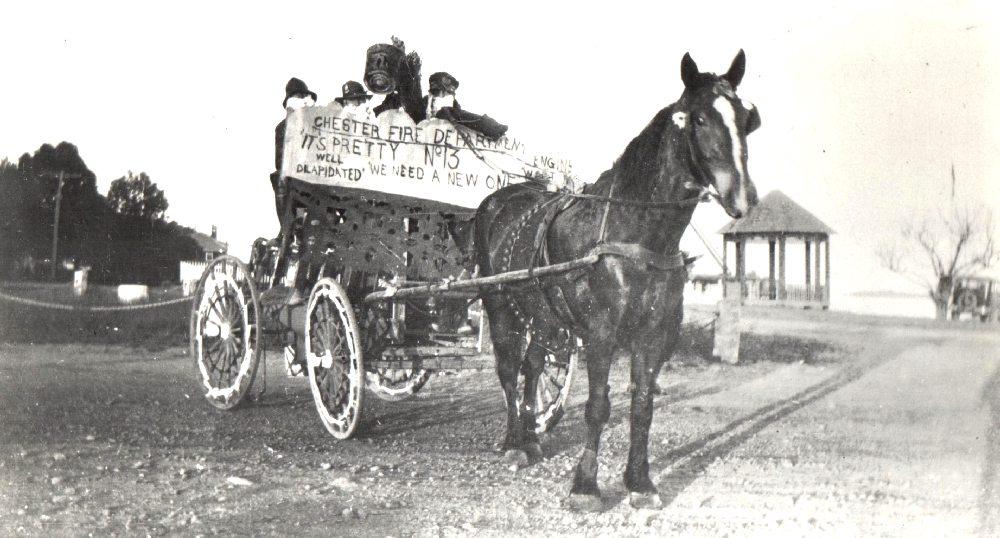"Une photo en noir et blanc d'un groupe de personnes sur un chariot tiré par des chevaux. Elles tiennent une pancarte où l'on peut lire, ""Chester Fire Department number 13 we need a new engine"". (La caserne 13 des pompiers de Chester a besoin d'un nouveau camion de pompiers.)"