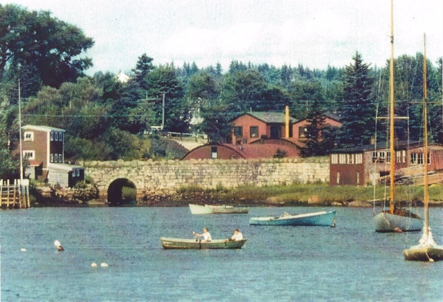 A colour photo with boats in the foreground looking from Mill Cove toward Hawboldt Gas Engines showing the old stone bridge, the red rounded foundry, machine shop and main office. A building on the left of the bridge was a storage building and the red buildings at the other end of the bridge were a woodworking shop. The stream came from Stanford Lake powering the foundry and supplying water for the village water system and empting into Mill Cove under the old stone bridge.