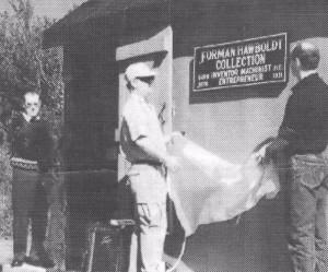 Une photo de journal en noir et blanc montrant l'ouverture officielle de La Collection de Forman Hawboldt. L'homme de gauche est Allen Bremner, au centre un représentant de la municipalité dévoile la plaque, à l'extrême droite se trouve Brad Armstrong, un membre de la famille.