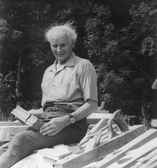 Black and white photograph of François-Xavier Lachance, aged, sitting outside on a pile of materials, holding a wooden molding.