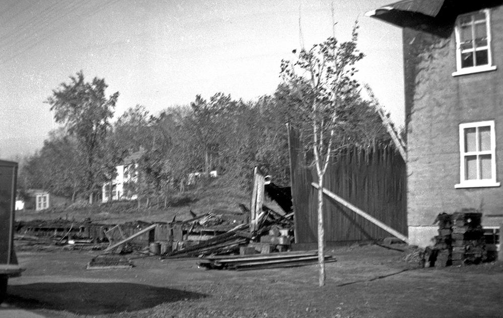 Photographie noir et blanc montrant la fondation d'un bâtiment, un mur de bois brûlé presque en entier et des planches brûlées au sol. Une résidence en pierre, dont le mur gauche et le toit de la maison sont noircis par le feu, est partiellement visible, à droite de l'image.