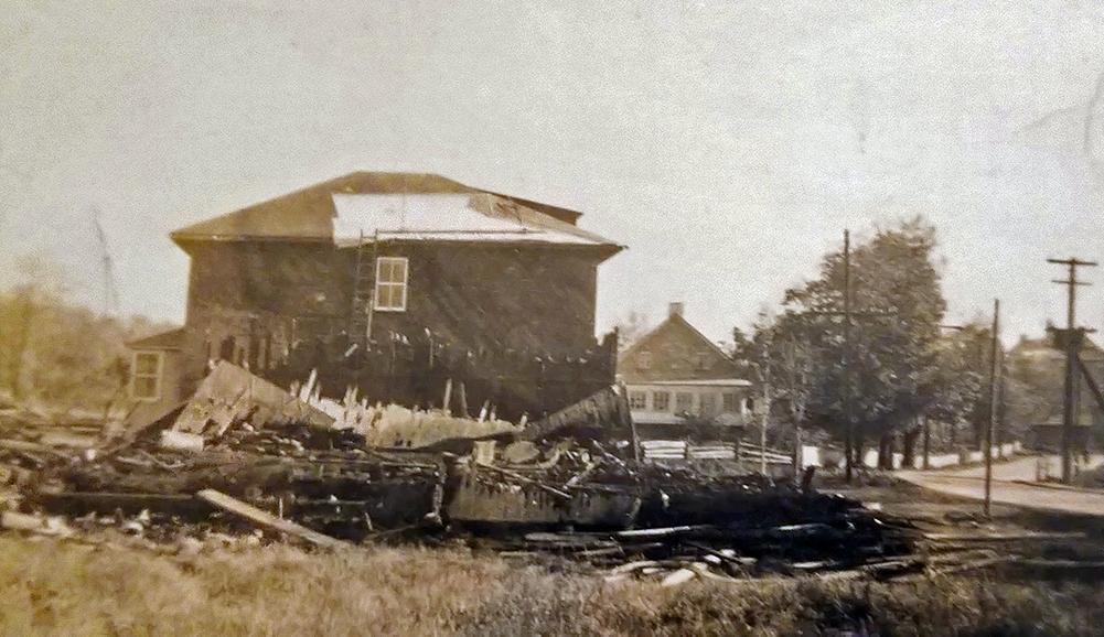 Photographie sépia montrant un amas de planches brûlées à l'avant-plan. Une résidence à deux étages endommagée par le feu est visible derrière les vestiges.