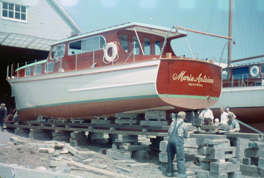 Color photograph where a white painted wooden yacht with mahogany cabin and aft is installed on blocks and boards at the exit of a hangar. The inscription