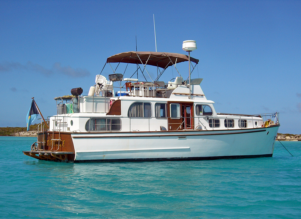Color photograph of a white yacht, profile, on a blue sea. The upper deck is converted into a terrace with barbecue and canvas shelter.