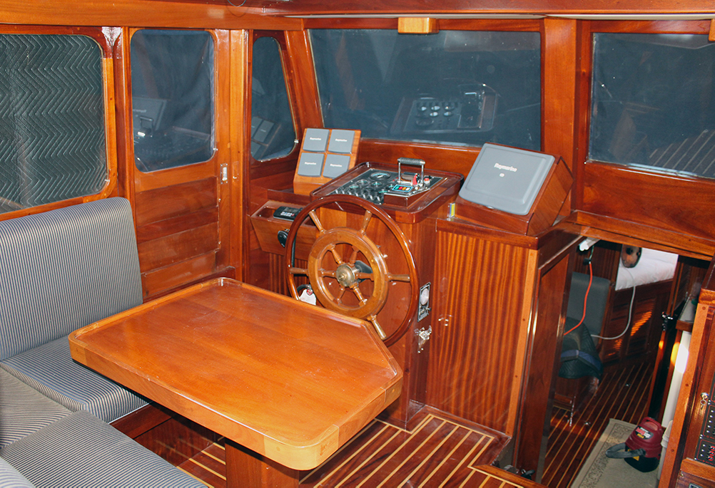Color photograph of the interior of a cabin, the surfaces of which are mahogany woodwork. In the center is the wheel, in front of the navigation instruments. A wooden table partly surrounded by a bench is in the foreground.