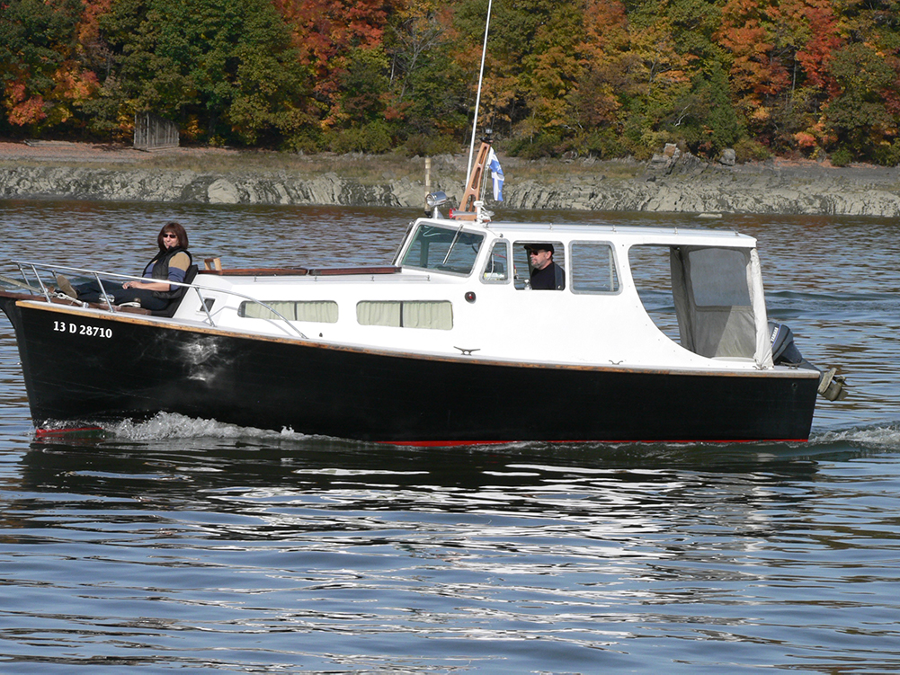 Color photograph of a small boat with black hull and white cabin, which sails in front of a rocky bank. A pilot is inside the cabin. A woman is sitting on the deck, at the front, smiling.