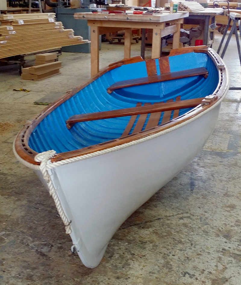 Color photograph of a white wooden boat with blue interior, front view in light dive-angle. The boat is placed on a concrete floor in a carpentry workshop.