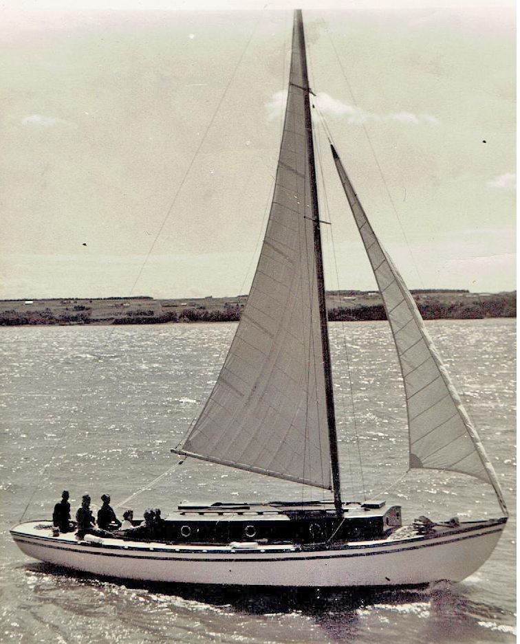 Photograph of a white sailboat with dark cabin, sailing sails deployed under the sun. Six people are on board. Fields are visible in the background.