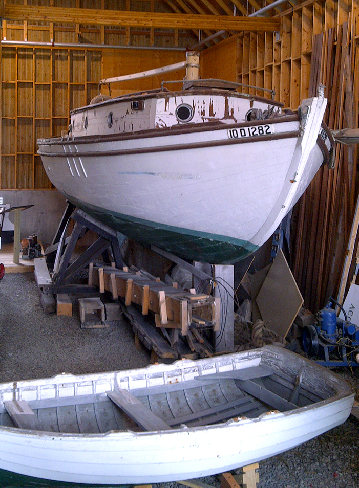 Color photograph of a white, brown and green wooden boat on a trestle inside a building.