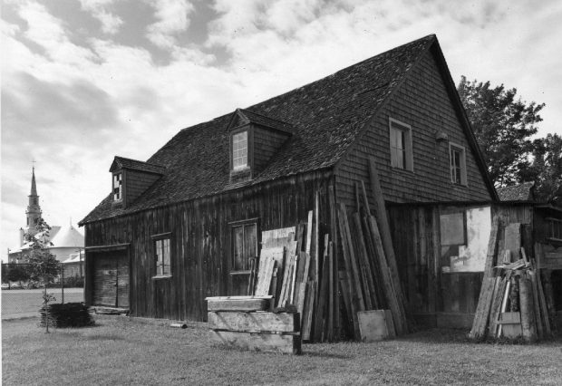 Black and white photograph of a wooden building and cedar shingles, with two dormers. Several boards and materials are backed on it. The church of Saint-Laurent is visible in the background, on the left.