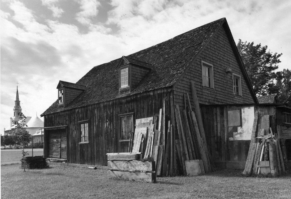 Photographie noir et blanc d'un bâtiment en bois et bardeaux de cèdre, muni de deux lucarnes. Plusieurs planches et matériaux y sont adossés. L'église de Saint-Laurent est visible à l'arrière-plan, à gauche.