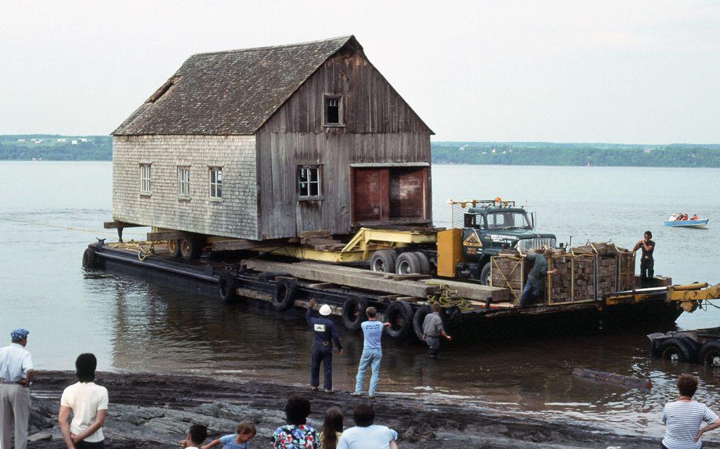 Photographie couleur montrant le déménagement par bateau d'une chalouperie en bois et bardeaux de cèdre. Le bâtiment est posé sur une remorque tirée par un camion, le tout monté sur une barge. Cinq travailleurs sont sur la barge ou près de la rive. Des curieux, enfants et adultes, observent la scène.