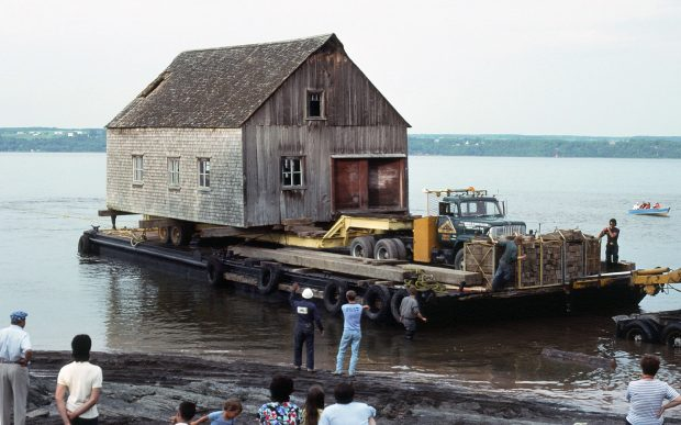 Color photograph showing the relocation by boat of a wooden and cedar shingles rowboat shop. The building sits on a trailer pulled by a truck, all mounted on a barge. Five workers are on the barge or near the shore. Curious children and adults watch the scene.