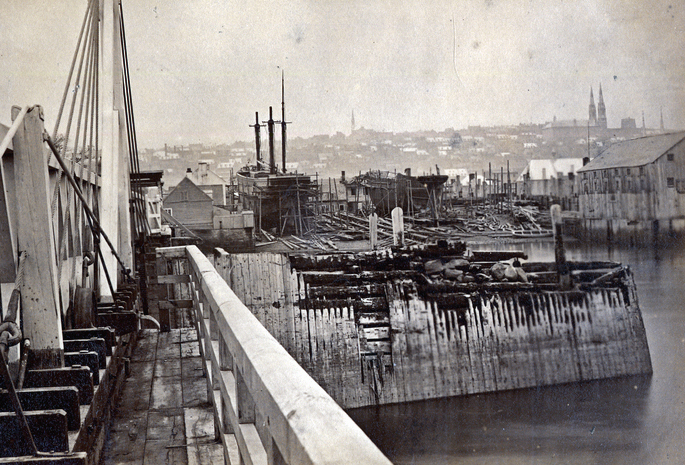 Black and white photograph of a shipyard. There is a dock in the foreground, as well as a sailboat with three masts and a second without mast in the center of the image. Large buildings are located on the water's edge on the right. The upper city of Quebec is visible in the background.