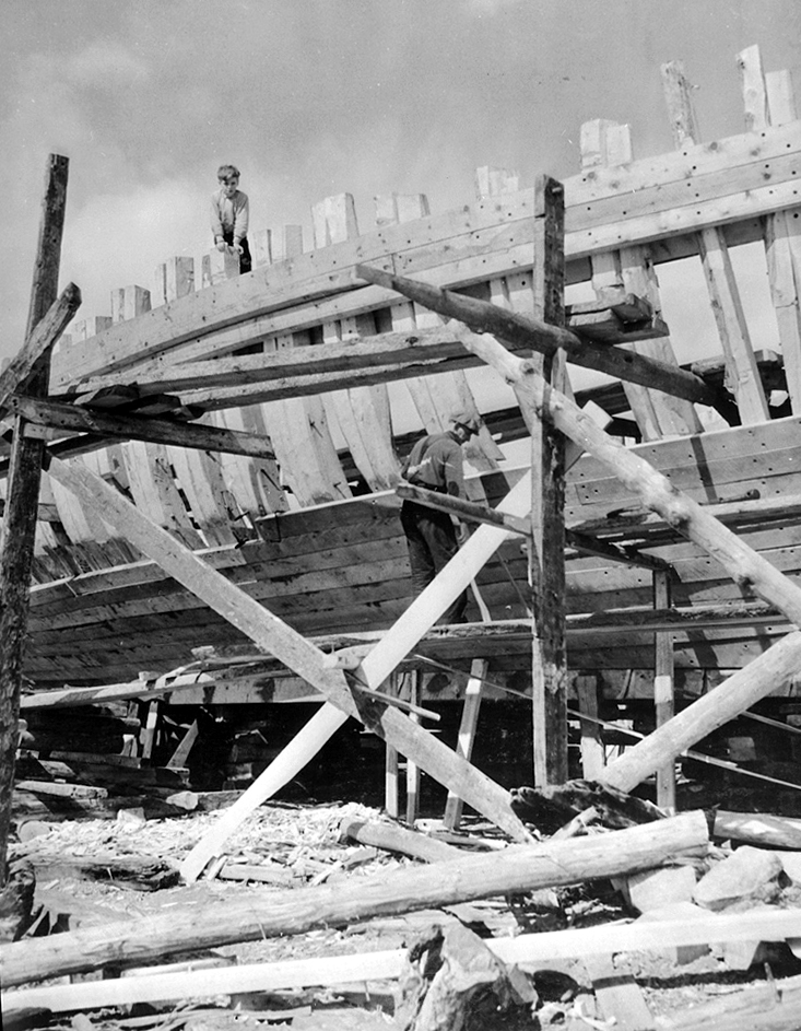 Black and white photograph of a man working to fix the siding of a large boat on pedestals. He is standing on a wooden scaffolding. A young boy is standing at the top of the hold structure.