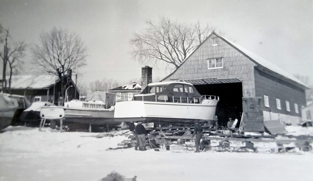 Black and white photograph showing a cruiser yacht mounted on a base in front of a building with a large door, in winter. Four men are busy around the boat on the ground. Other boats are visible on the left.