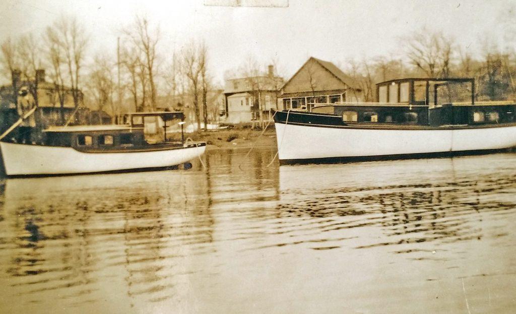 Photographie sépia de deux bateaux de bois, avec cabine, ancrés près de la rive. Des maisons et des arbres sans feuillage sont à l'arrière-plan.