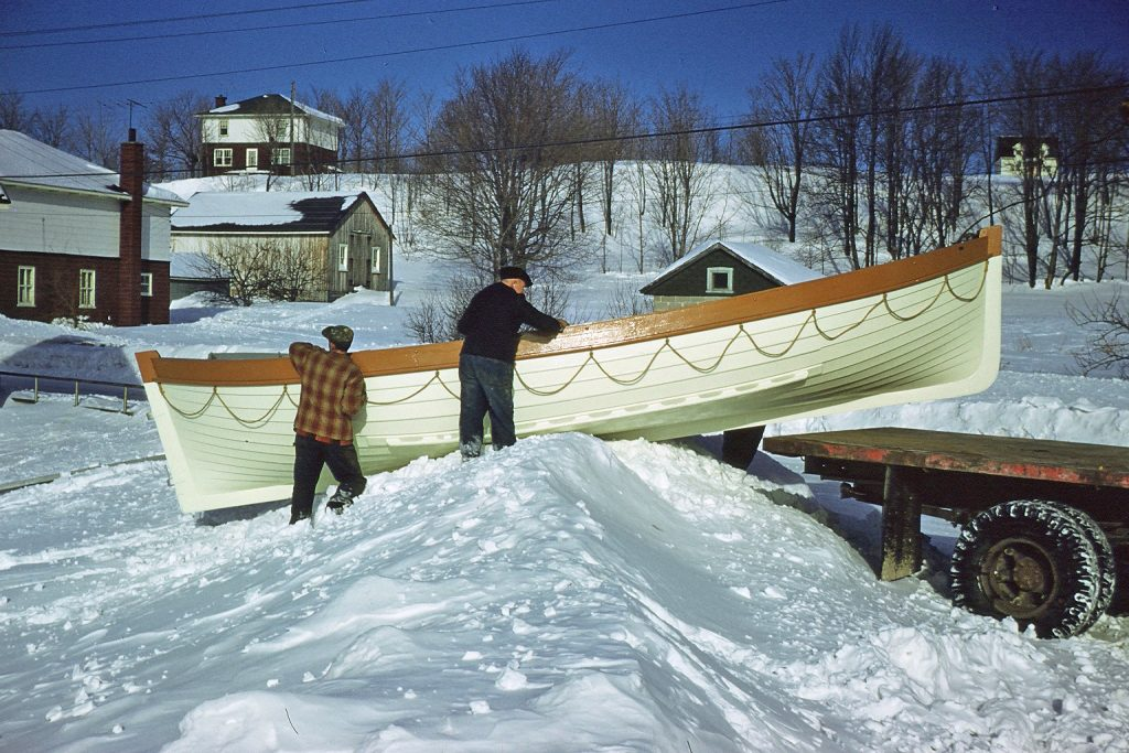Color photograph where two men, one young and one elderly, slide a white boat on a pile of snow to install it on the rear platform of a truck.