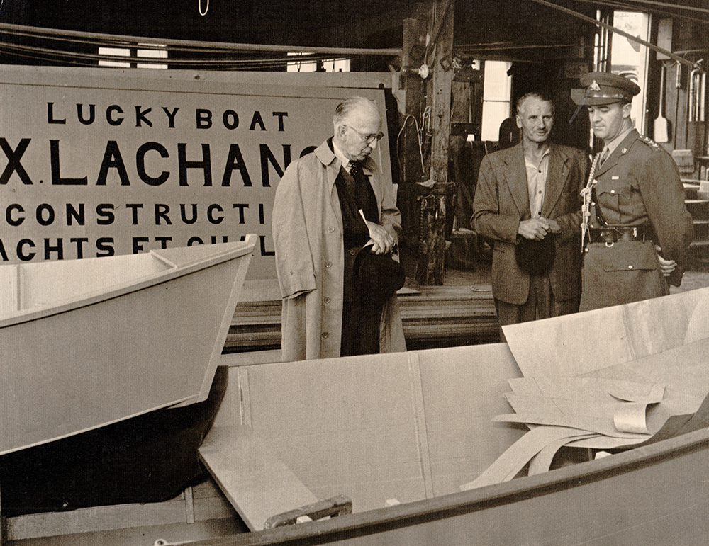 Black and white photograph where three men stand in a rowboat shop. A sign bearing the inscription
