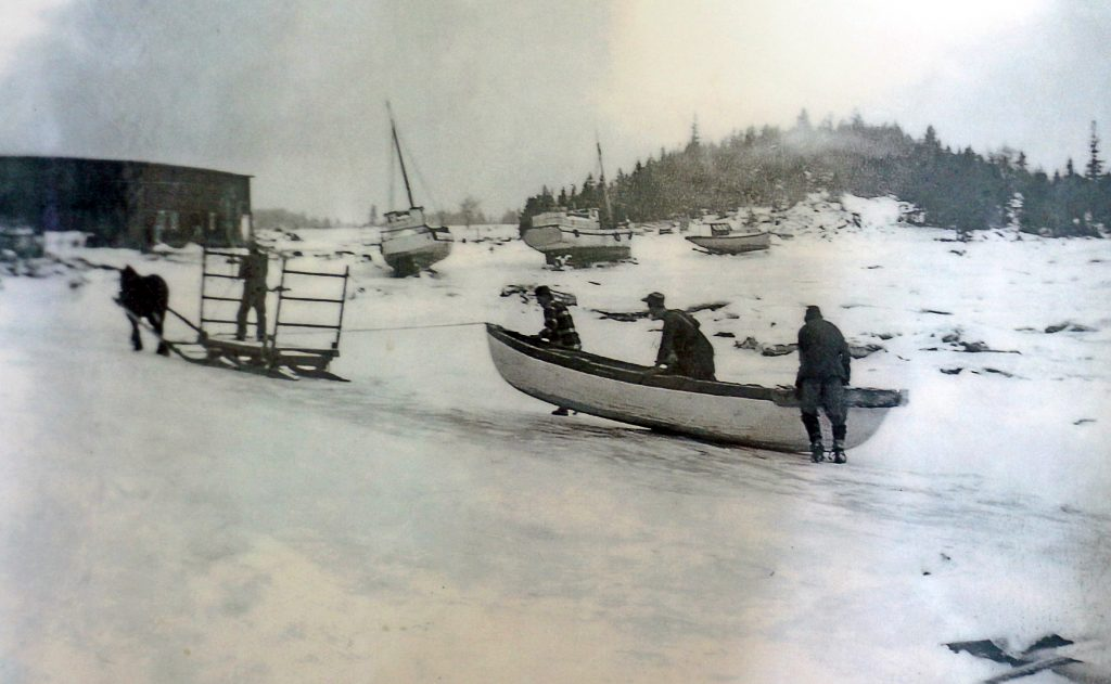 Black and white photograph where three men push a rowboat on the snowy shore. The boat is tied behind a sledge pulled by a horse on which stands a coachman. In the background are a building and three sailboats on the shore.