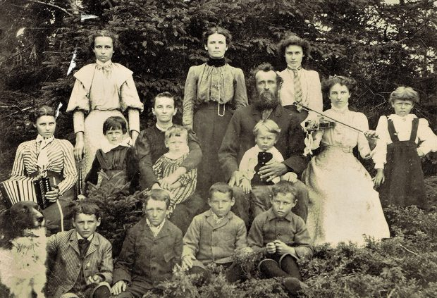 Black and white photograph showing the parents of François-Xavier Lachance, their 13 children and their dog. All look at the camera, sitting or standing in front of a woodlot.