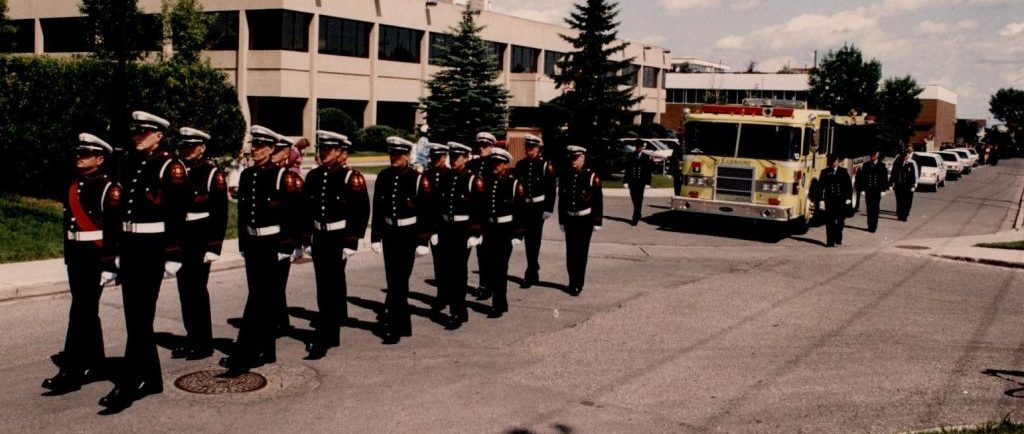 Several members of the Guard of Honor walk in uniform in front of a yellow fire truck at the head of Morley James' funeral procession.