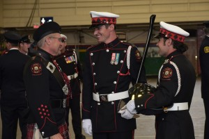 Two Honour Guard Members and a piper from Pipes and Drums, all in full uniform, laugh as they talk together.