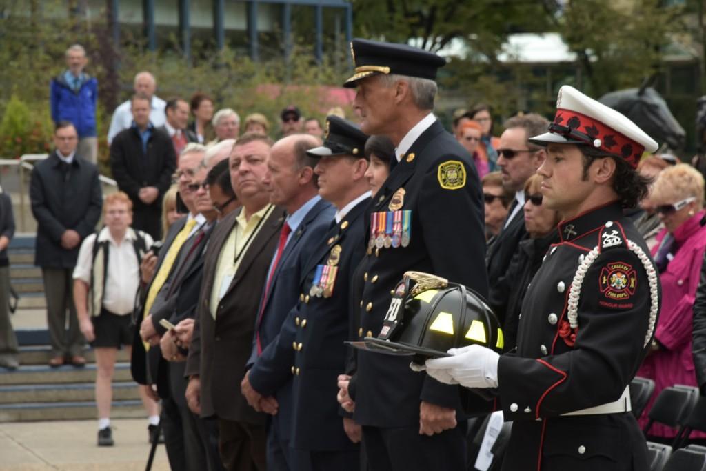 John Judge, garde d'honneur en uniforme de grande tenue et gants blancs, tient le casque commémoratif orné d'insignes jaunes à la place de l'hommage (Tribute Plaza). En arrière-plan, on aperçoit le chef du service d'incendie et la foule.