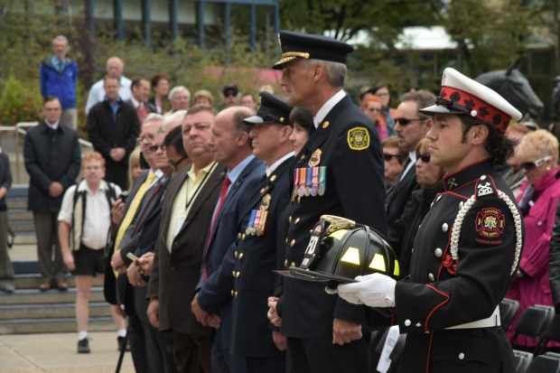 Guardsman John Judge in full uniform and white gloves holds black ceremonial helmet with yellow patches at Tribute Plaza with chief and crowd in background.